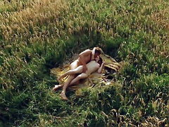 Carice van Houten lying naked with a guy in a field of tall grass, lying on a blanket as she..