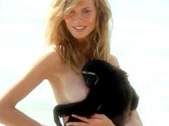 Sexy blonde Heidi Klum topless posing with black monkey on beach