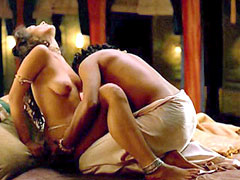 Indira Varma nude lays on bed while..