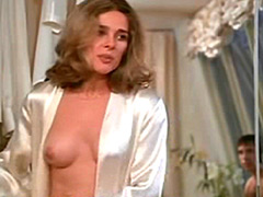 Joan Hackett putting on see-through blouse without bra