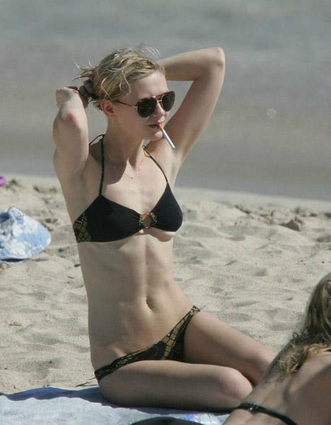 Kirsten Dunst sunbathing in sexy black bikini on beach ...