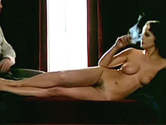 Celebrity Laura Antonelli fully naked laying on a bed and smoking