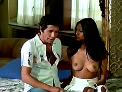 Laura Gemser topless sits on sofa and..